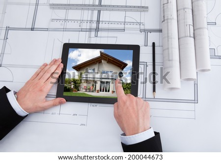 Cropped image of male architect using digital tablet on blueprint in office
