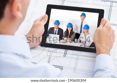 Cropped image of male architect video conferencing with team through digital tablet in office - stock photo