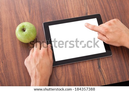 Cropped image of male college student using blank digital tablet by green apple on table - stock photo