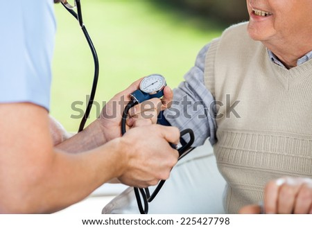 Cropped image of male doctor Checking blood pressure of senior man at nursing home - stock photo