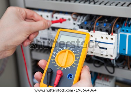 Cropped image of male electrician examining fusebox with digital insulation resistance tester - stock photo