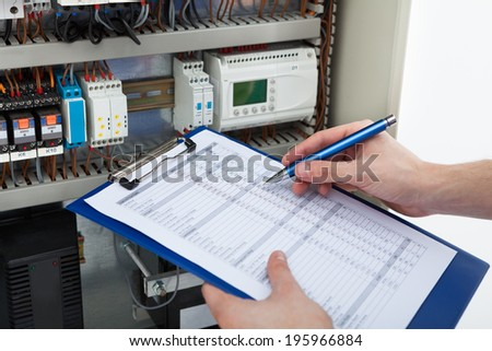 Cropped image of male electrician holding clipboard while examining fusebox - stock photo