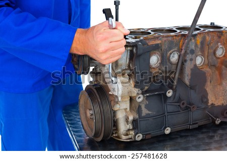 Cropped image of male mechanic repairing car engine on white background - stock photo