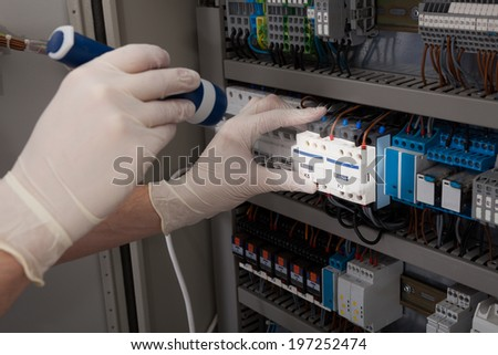 Cropped image of male technician analyzing fusebox with flashlight