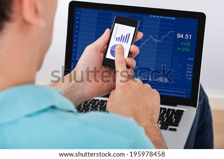 Cropped image of man analyzing stock market using smartphone and laptop at home - stock photo