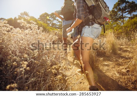 Cropped image of man and woman walking on country trail path. Young couple hiking on mountain on sunny day.