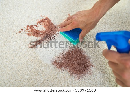 Cropped image of man cleaning stain on carpet with sponge - stock photo