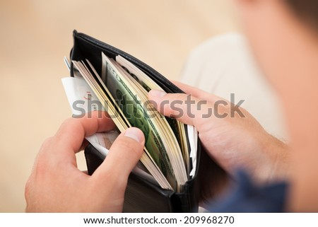 Cropped image of man holding wallet with banknotes at home - stock photo