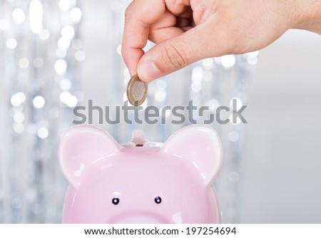 Cropped image of man inserting coin in piggybank indoors - stock photo