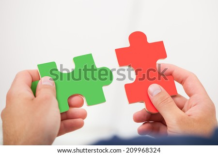 Cropped image of man joining puzzle pieces at home