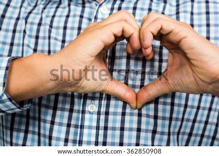 Cropped image of man making heart shape with hands