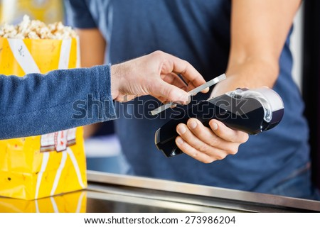 Cropped image of man making payment through smartphone using NFC technology at cinema - stock photo