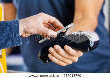 Cropped image of man paying through smartphone using NFC technology at cinema - stock photo