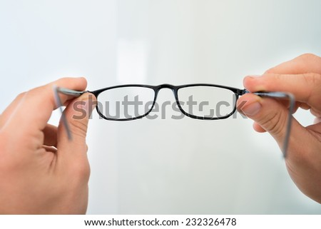 Cropped image of man's hands holding eyeglasses
