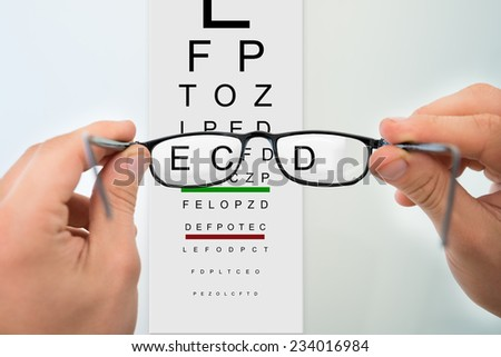 Cropped image of man's hands holding eyeglasses against eyesight test chart - stock photo