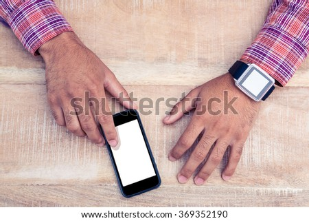 Cropped image of man using smart phone on table