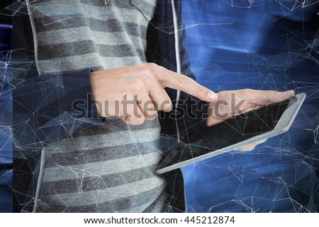 Cropped image of man using tablet against black background with shiny hexagons - stock photo