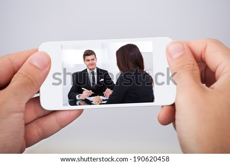 Cropped image of man watching movie on smart phone - stock photo