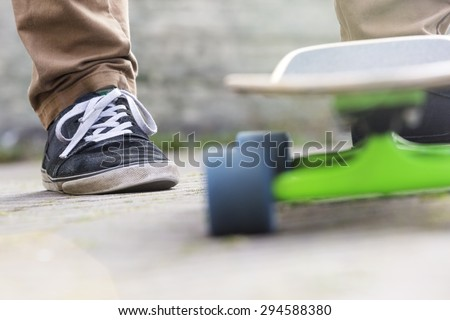 Cropped image of man with skateboard on footpath - stock photo