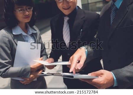 Cropped image of manager showing document to his colleagues - stock photo