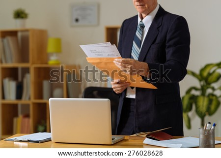 Cropped image of mature businessman reading correspondence in the office
