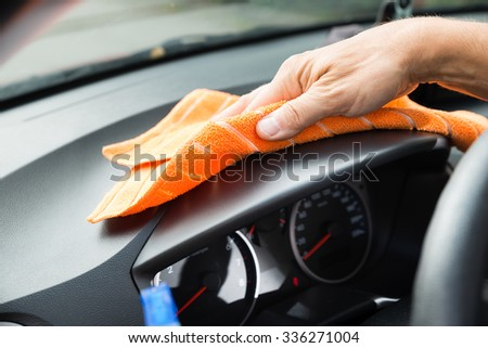 Cropped image of mature male worker cleaning car dashboard - stock photo