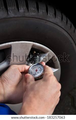 Cropped image of mechanic checking tire pressure using gauge