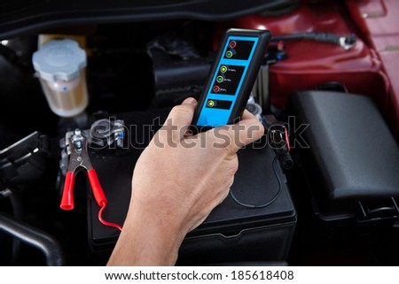 Cropped image of mechanic testing car battery - stock photo
