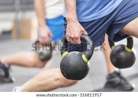 Cropped image of men lifting kettlebells at gym