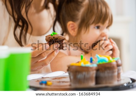 Cropped image of mother holding cupcake with girl eating cake at birthday party - stock photo