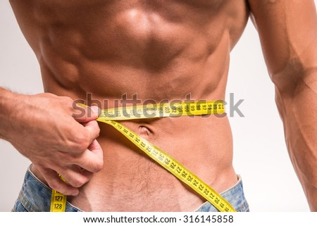 Cropped image of muscular man is measuring his waist with measuring tape. - stock photo