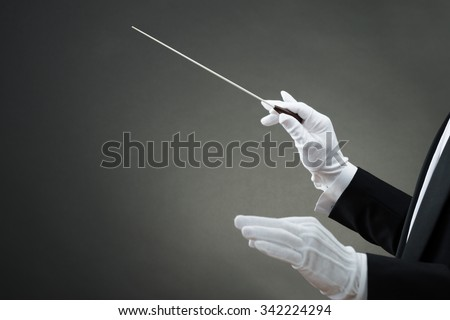 Cropped image of music conductor's hand instructing with baton against gray background - stock photo