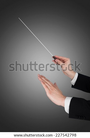 Cropped image of music conductor's hands holding baton against gray background - stock photo