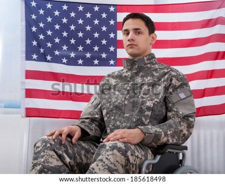 Cropped image of patriotic soldier sitting on wheel chair against American flag - stock photo