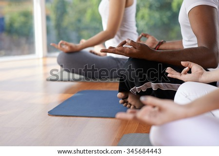 Cropped image of people meditating in lotus position