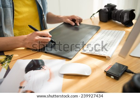 Cropped image of photographer retouching a photo - stock photo