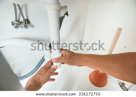 Cropped image of plumber working on pipes under kitchen sink