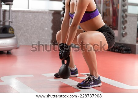 Cropped image of professional sportswoman doing kettlebell weight exercise - stock photo