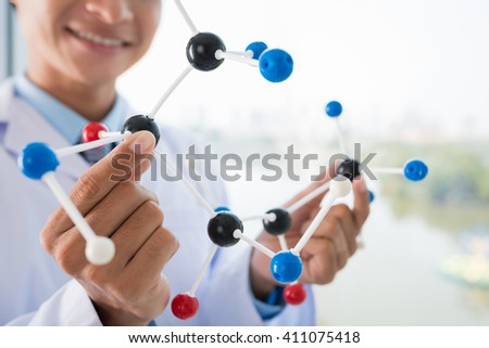 Cropped image of  scientist holding plastic molecular structure - stock photo