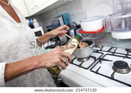 Cropped image of senior woman adding olive oil to saucepan at kitchen counter - stock photo