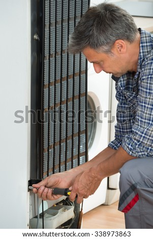 Cropped image of serviceman working on fridge with screwdriver at home