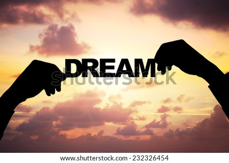 Cropped image of silhouette businessman's hands holding DREAM word against cloudy sky during sunset - stock photo