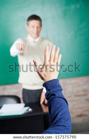 Cropped image of student's hand with professor pointing at him in classroom - stock photo
