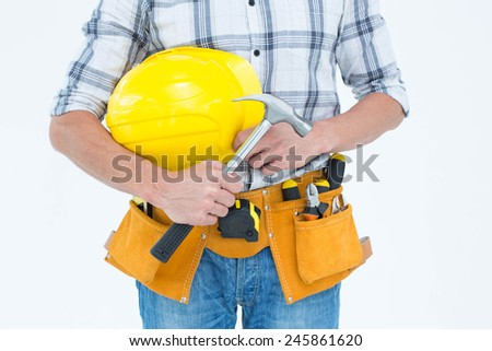 Cropped image of technician holding hammer and hard hat over white background - stock photo