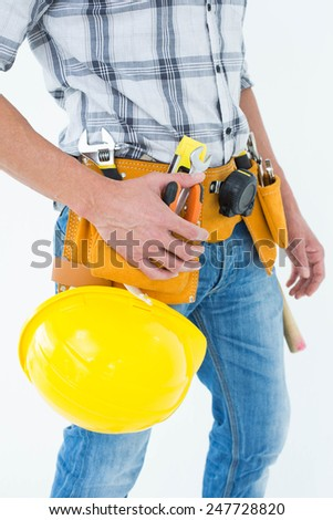 Cropped image of technician with tool belt around waist and hard hat against white background