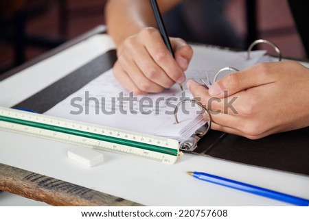 Cropped image of teenage schoolboy copying at desk during examination - stock photo