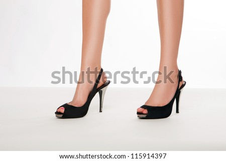Cropped image of the beautiful shapely smooth legs of a woman in stylish black leather stilettoes with open toes and straps