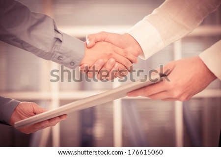 Cropped image of two businessmen handshaking in the sign of success dealing on the foreground  - stock photo