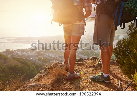 Cropped image of two hikers legs standing on a hiking path and looking at the view - stock photo