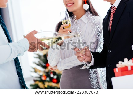 Cropped image of waiter pouring champagne into a flute at the Christmas party